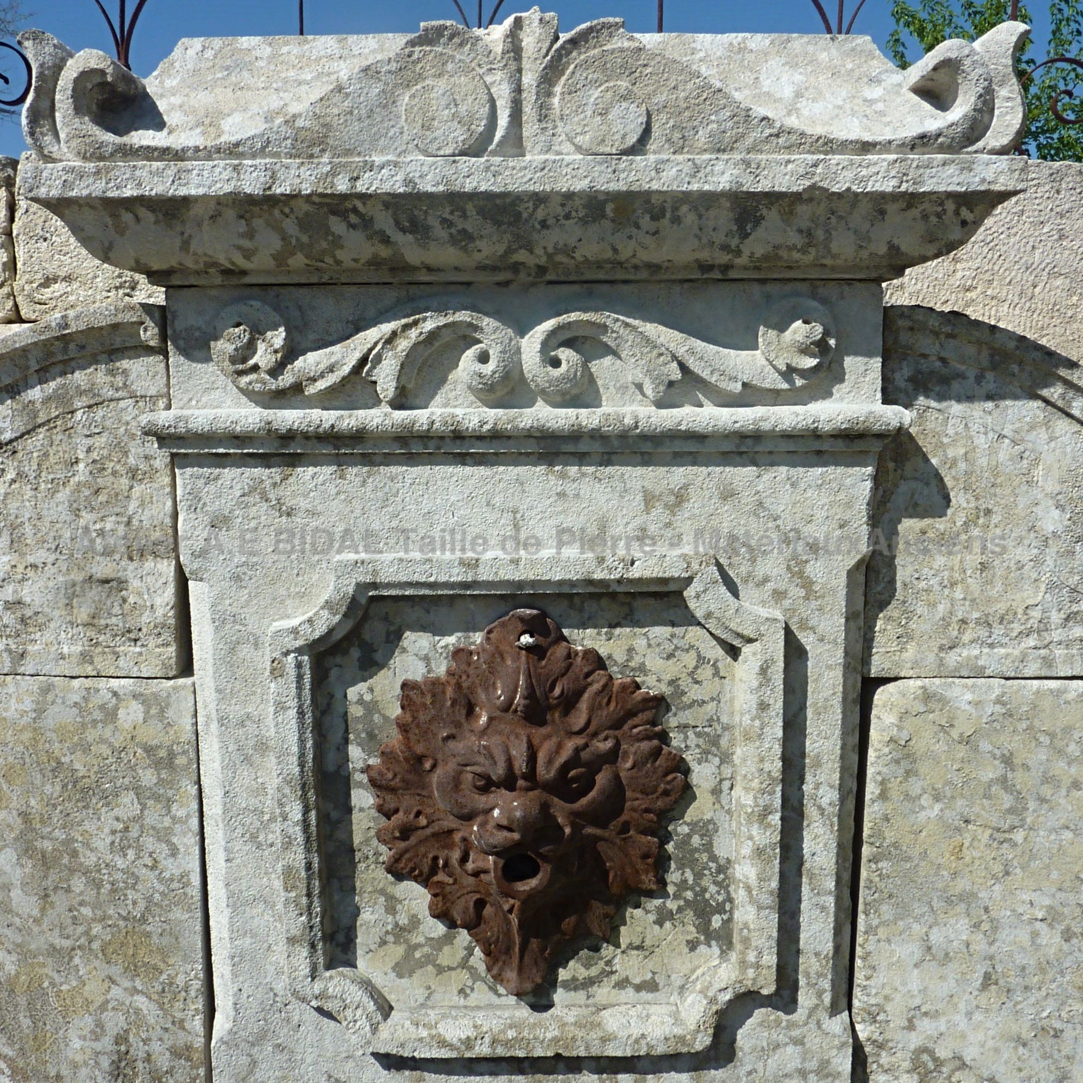 Detail of the cast iron water outlet on our old stone wall fountain | Stone fountain with cast iron lion's head.