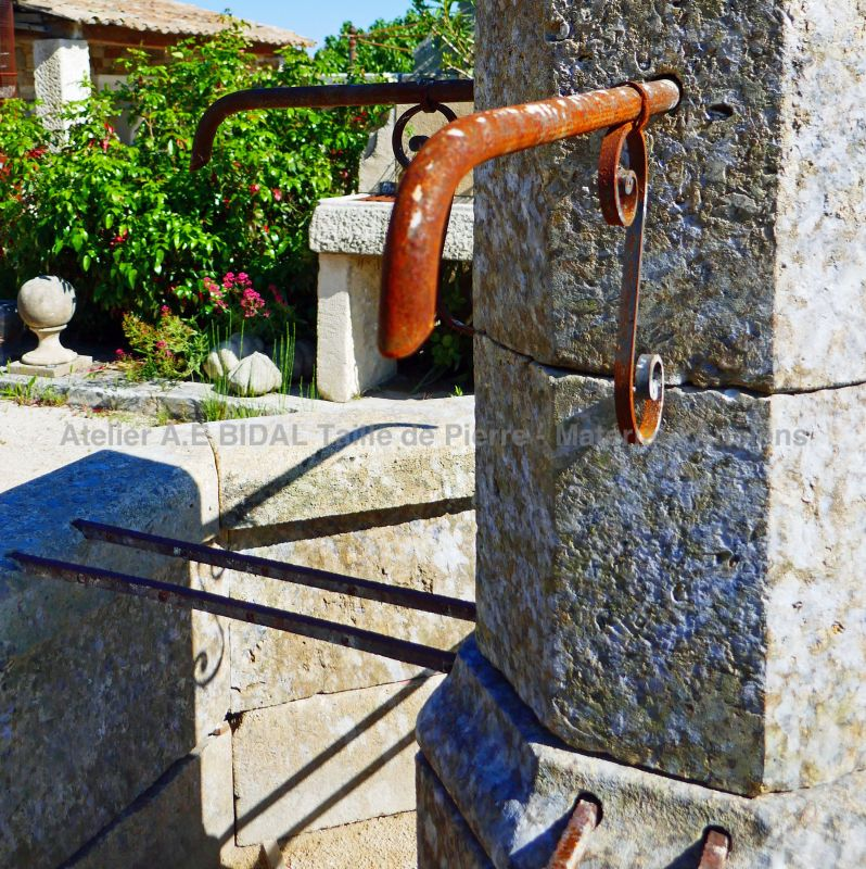 Detail of the forged water outlet from our natural stone fountain of Provence.
