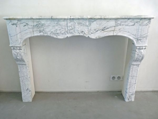 Fireplace in white marble and nicely carved and decorated - old fireplace with an elegant look.