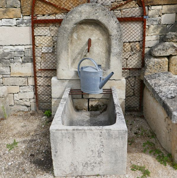 Small fountain with antique trough and monolithic pediment | Rustic wall fountain for garden.