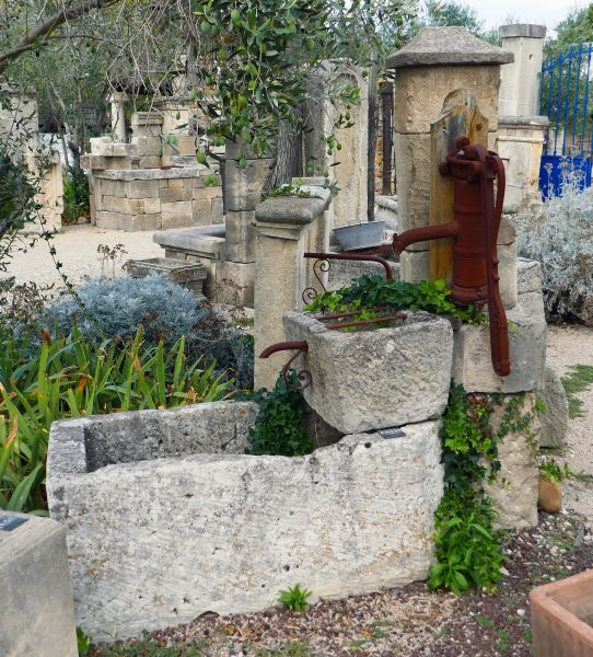 Beautiful garden fountain in aged natural stone and antique cast iron | Outdoor fountain with two stone troughs and an authentic cast iron hand pump.