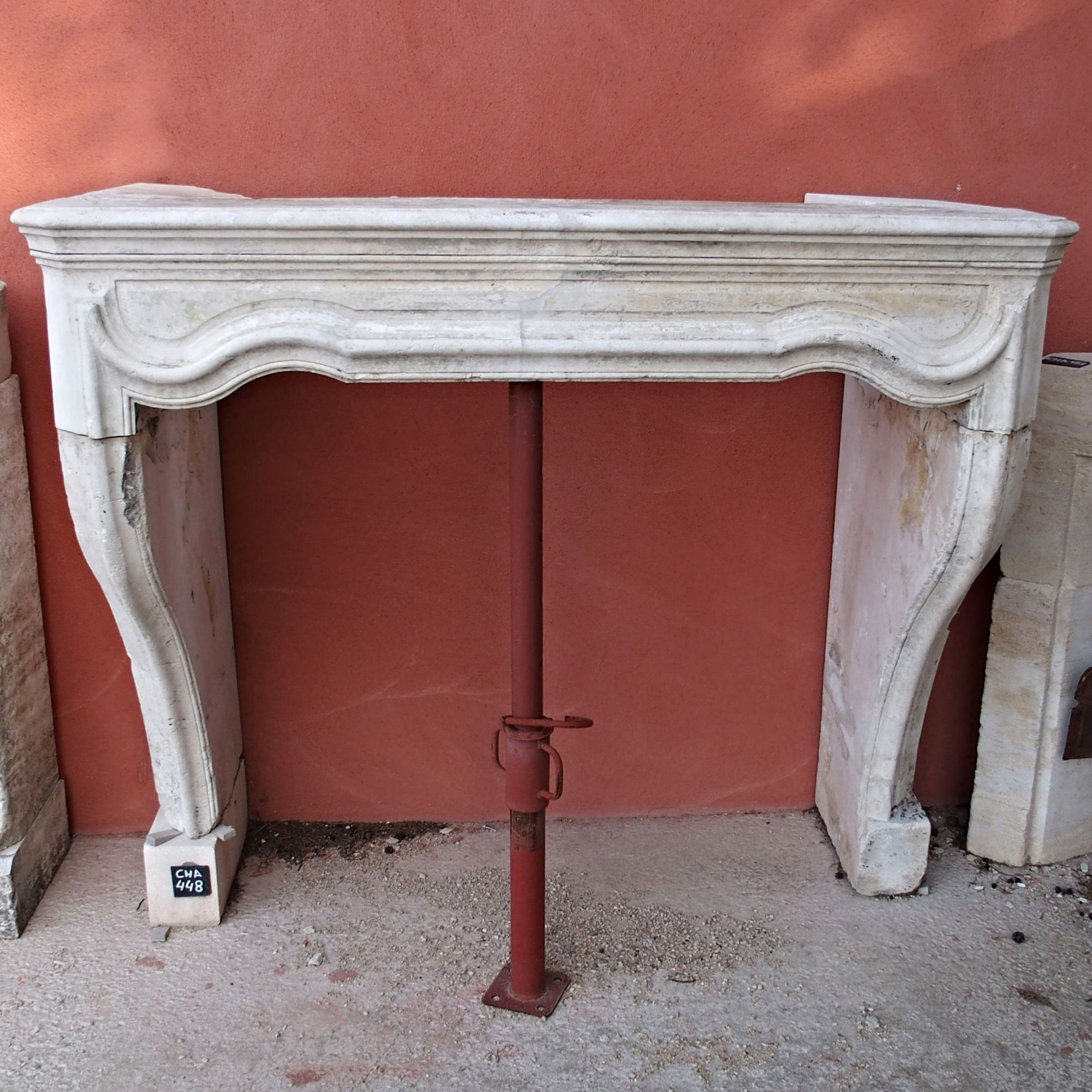 Old fireplace made of white stone - an old stone fireplace with a refined style with curves.
