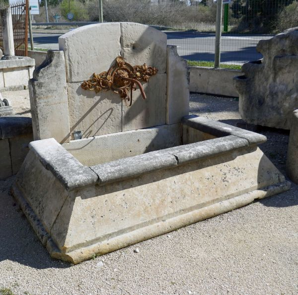 Antique stone fountain with cast-iron rosette and a stone basin with splayed edges.