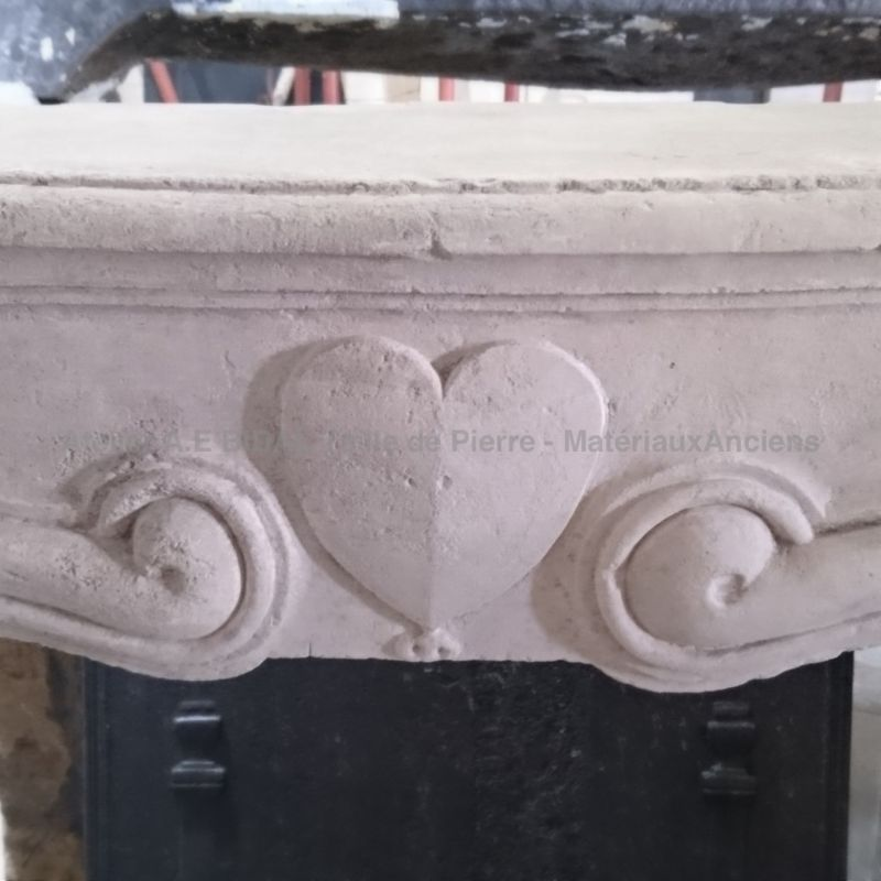 Antique stone fireplace called wedding - Antique fireplace decorated with a sculpted heart.
