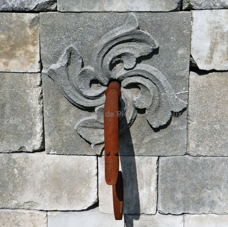 Detail of the wrought iron water outlet on the stone pediment of our garden fountain | Alain BIDAL