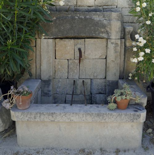 Wall fountain made of authentic old stone and wrought iron - ornamental fountain naturally weathered.