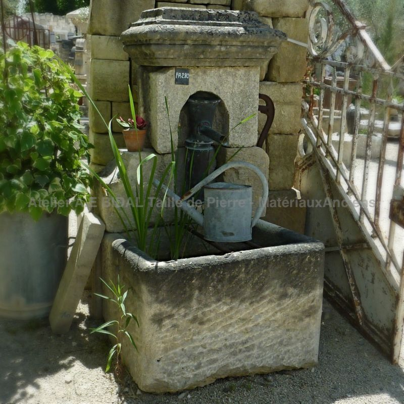 Small outdoor fountain with antique stone trough | Charming garden fountain with rectangular trough and old hand pump.