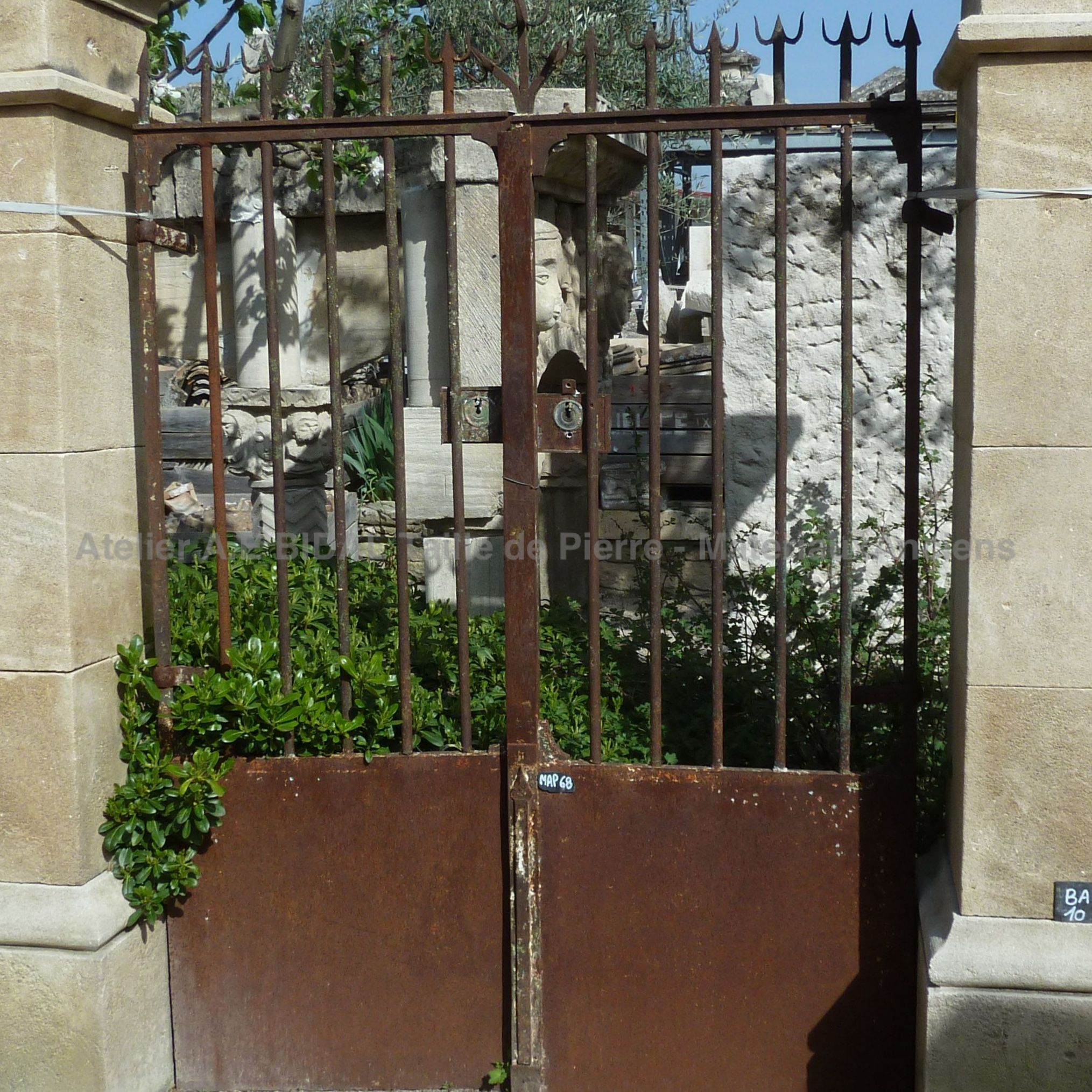 Small old wrought iron gate with 2 gates - pedestrian gate made of iron .