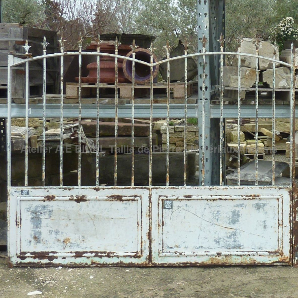 Antique gate made of wrought iron, white weathered by rust.