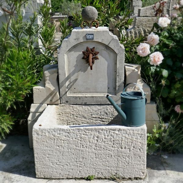 This charming wall fountain crafted in old stones is a beautiful wall fountain for the garden.