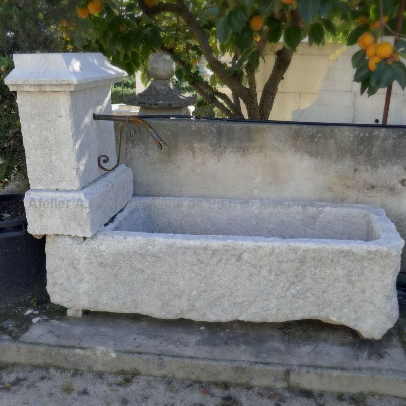 Country-style fountain in white stone for garden landscaping.