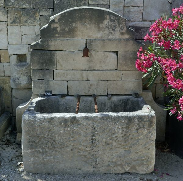 Outdoor fountain with antique stone trough and pediment in stone.