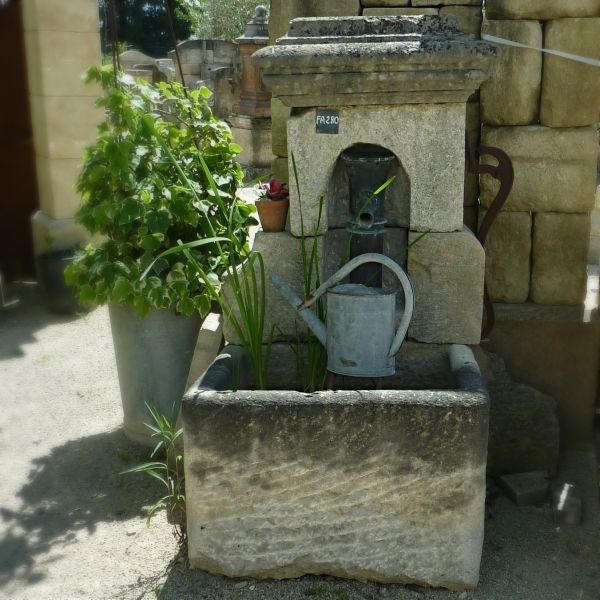 Garden fountain with hand pump | Old fountain with rectangular stone trough and manual cast iron pump.