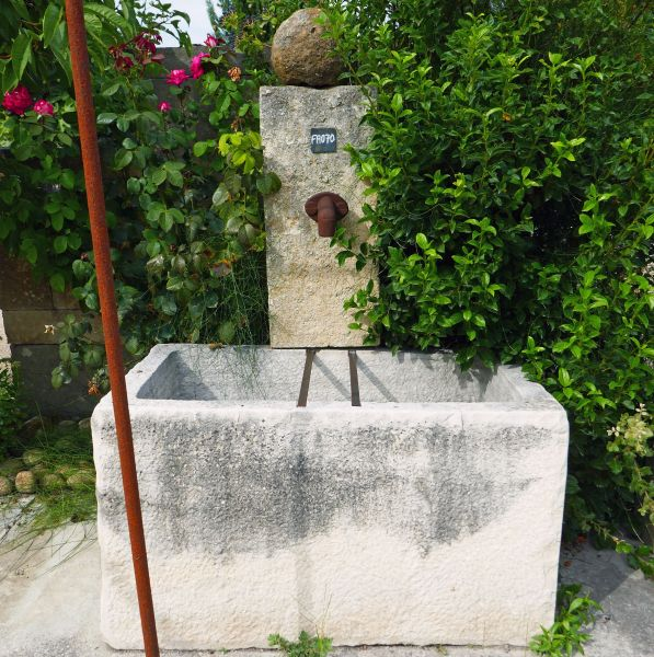 Antique garden fountain with old trough in stone on sale at Alain Bidal, stonemason in Provence.