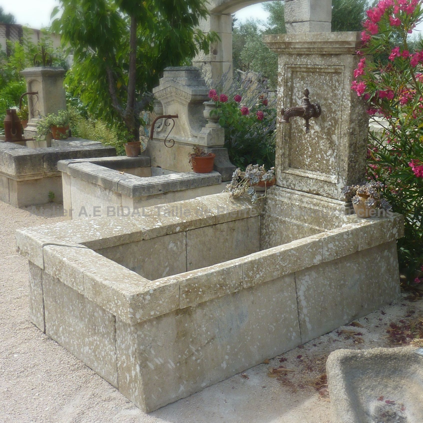 Large stone wall fountain : an outdoor fountain with wash-house-like basin in ancient stones.