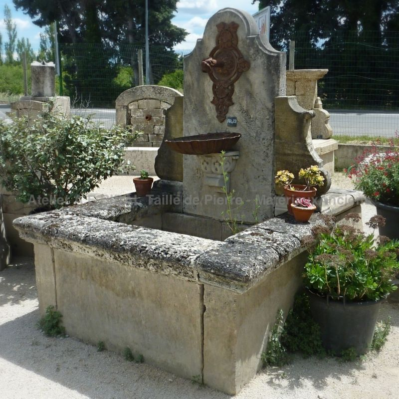 Patinated stone wall fountain | Garden fountain with basin and pediment in reclaimed elements.