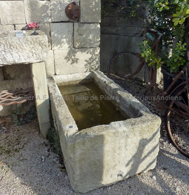 Antique monolithic stone trough on our garden wall fountain in old stones.