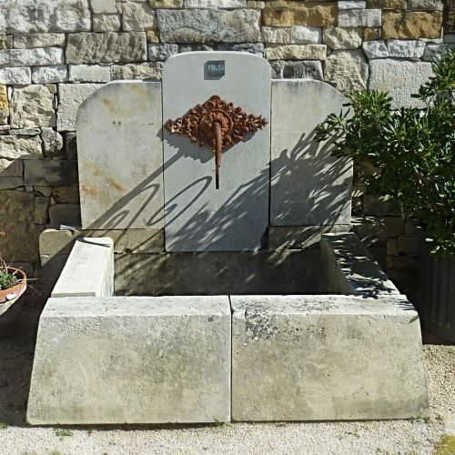 Stone wall fountain with beautiful iron palmette on its pediment.