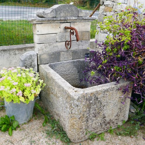 Outdoor fountain with antique trough | Old wall fountain decorated with a stone pediment.
