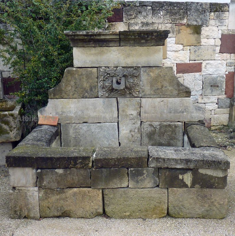 Beautiful rustic wall fountain with a sculpted water point on its front - beautiful outdoor fountain with rectangular basin.