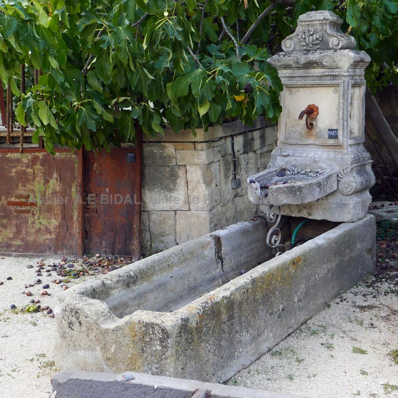 Large wall fountain with old trough and pediment with iron rosette.