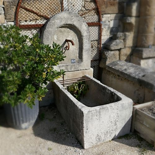 Old fountain of Provence in stone for the decoration of the garden.