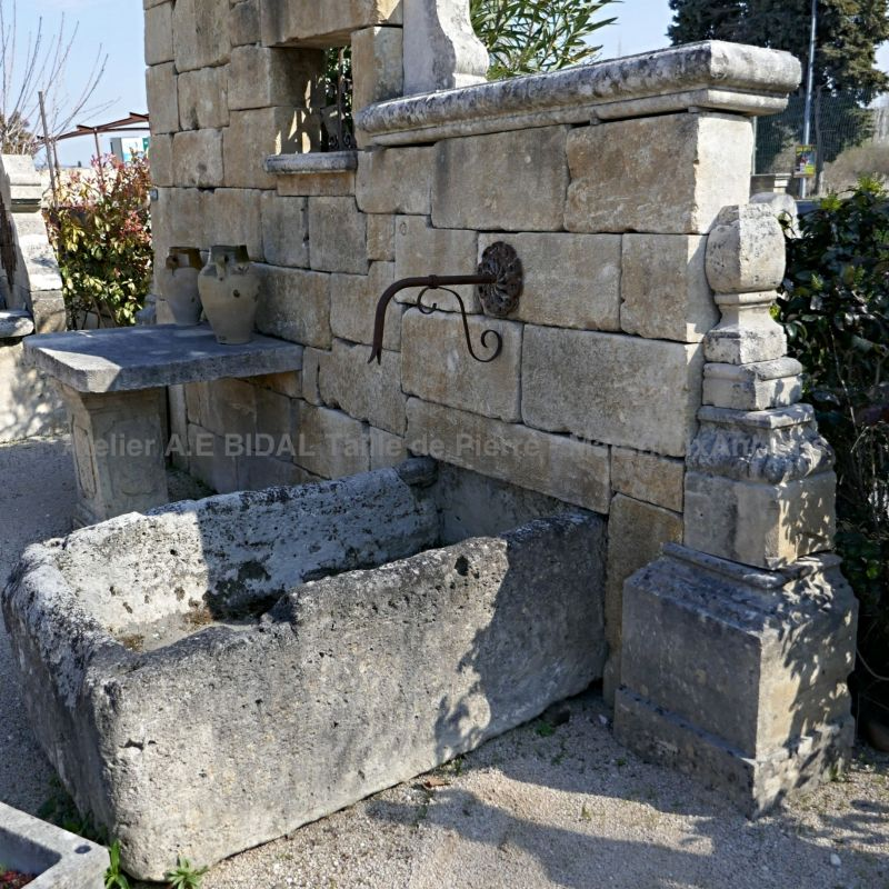 Antique stone fountain with low wall, table, pergola and basin