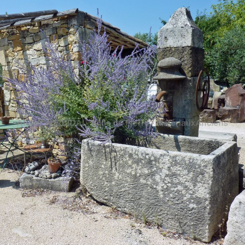 Stone wall fountain sold with its vintage hand pump made of cast iron.