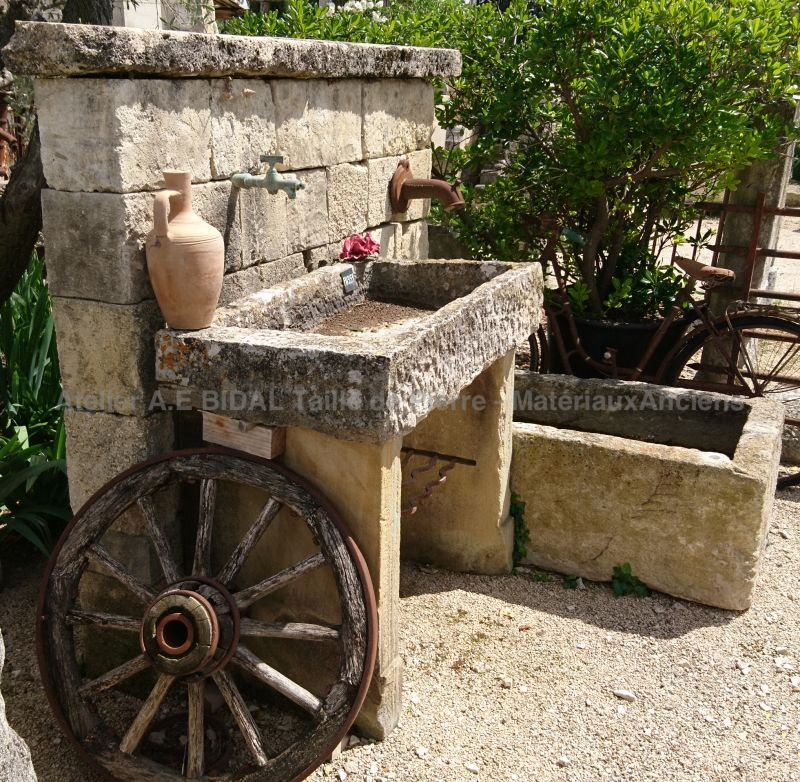 Wall stone fountain | Garden fountain with old trough and antique sink in stone.