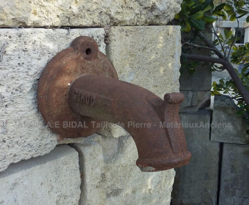 Old water outlet in cast iron on our antique wall fountain in stone.