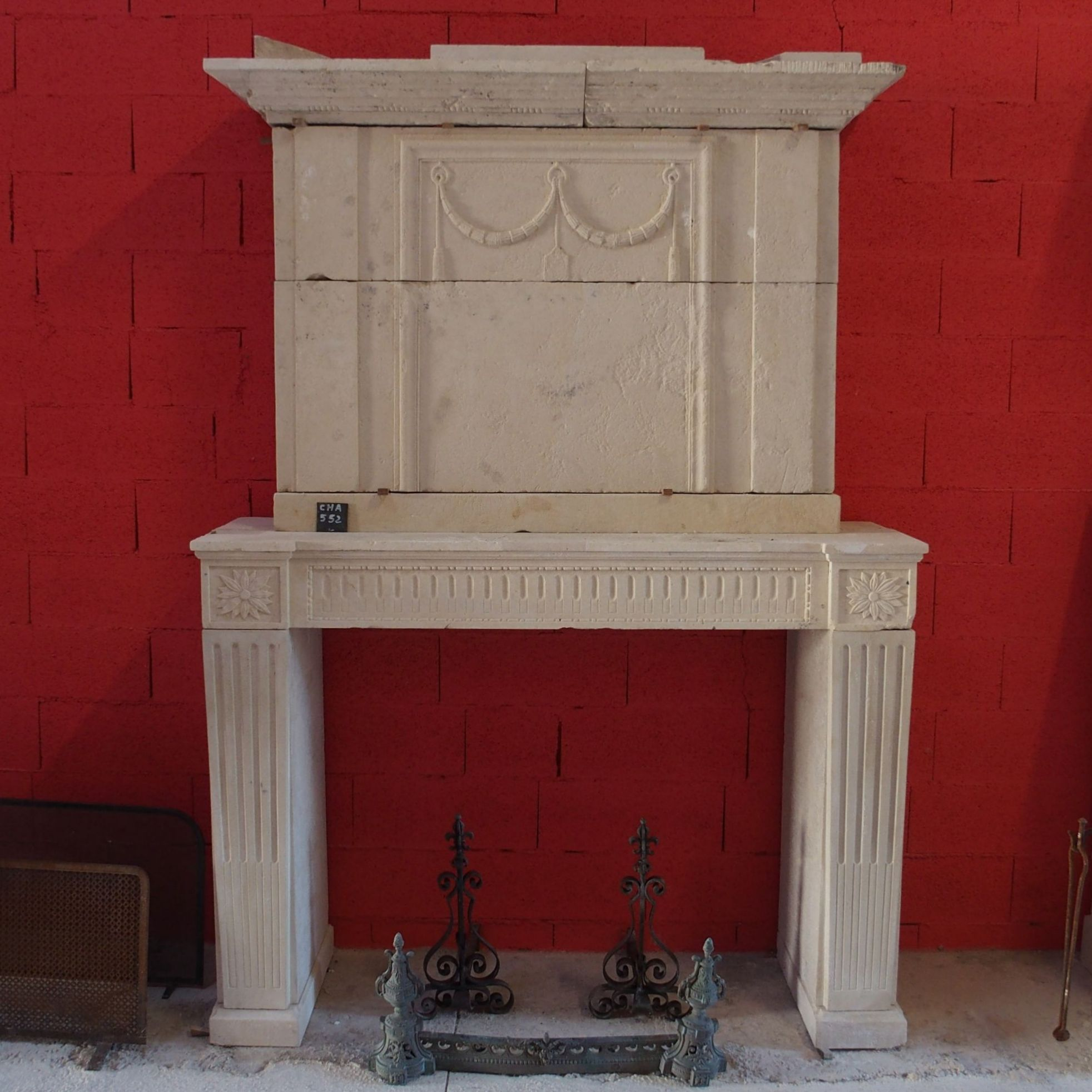 Old fireplace with an overmantle in an yellow-ochre color.