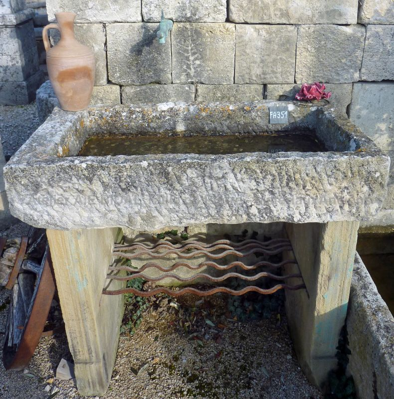 Antique monolith stone sink on our garden wall fountain in old stones.