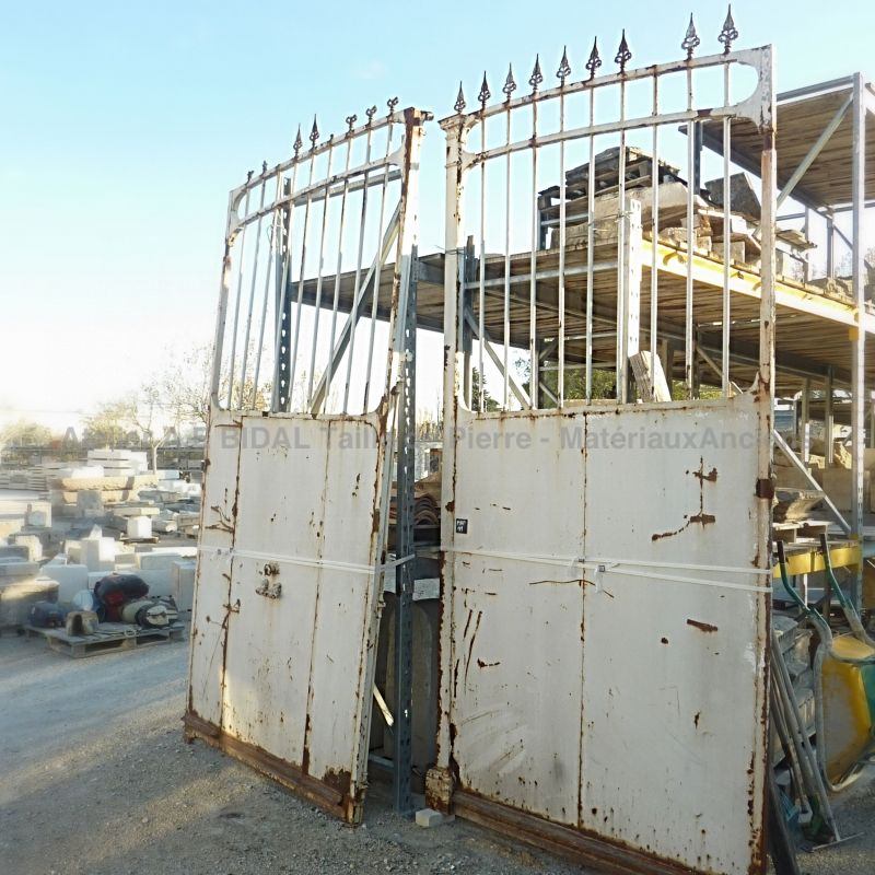 Antique wrought iron gate with a small gate for pedestrian passage.