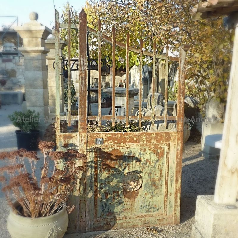 Antique wrought iron gate of rural charm with fixed frame.