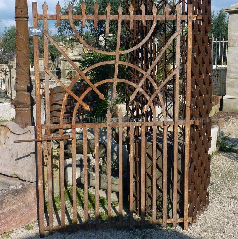 Old wrought iron gate in an elegant and rustic style - old gate decorated with arrows and semi circle.