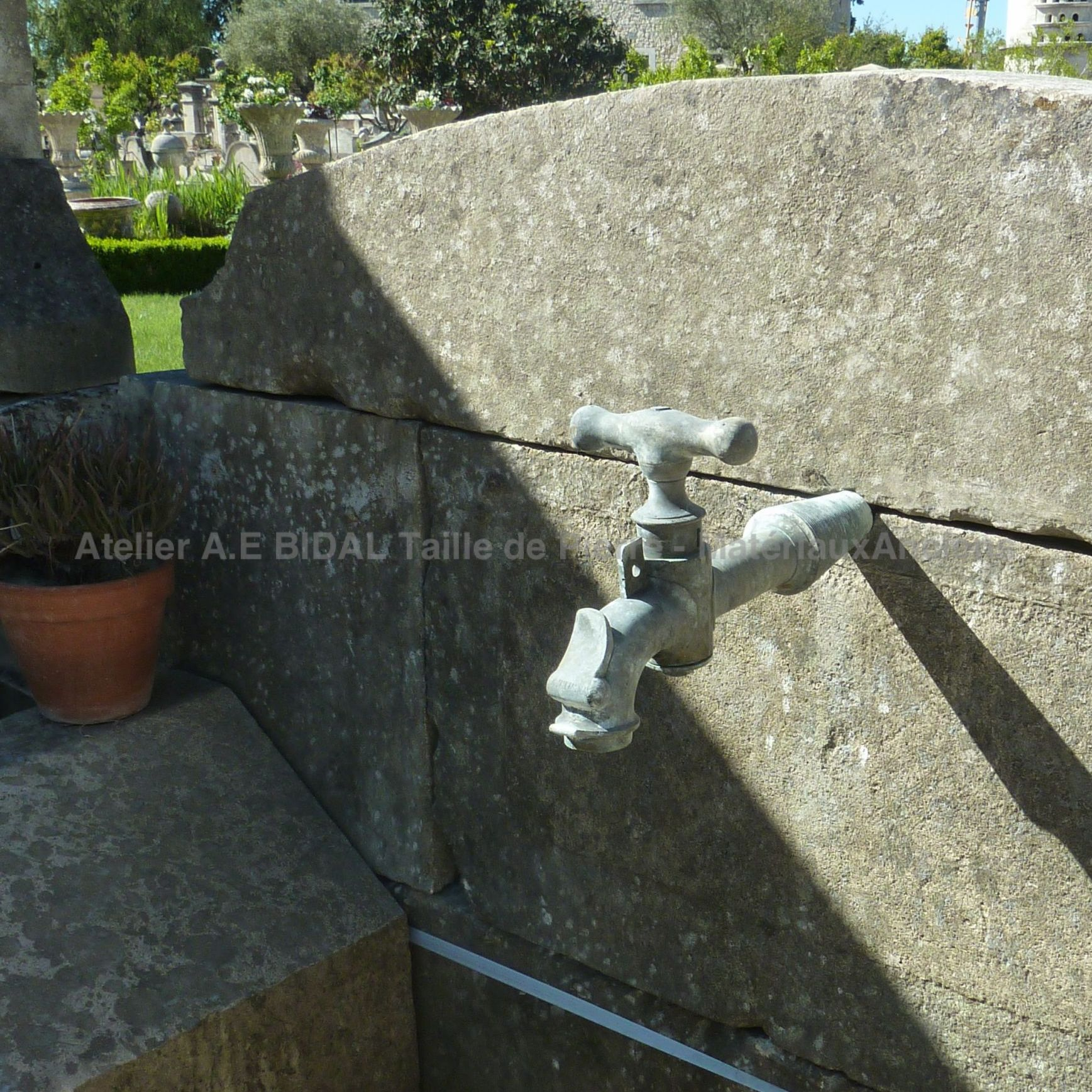 Antique metallic water tap on an outdoor fountain with wash house style basin.