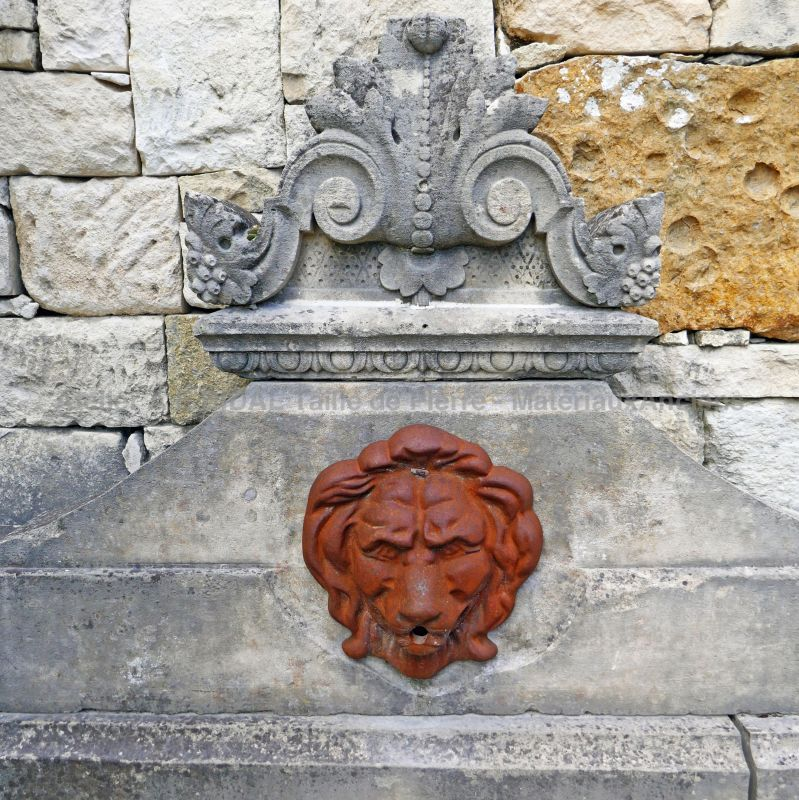 Detail of the cast iron lion head and finely hand-carved stone capital on our wall fountain of Provence.
