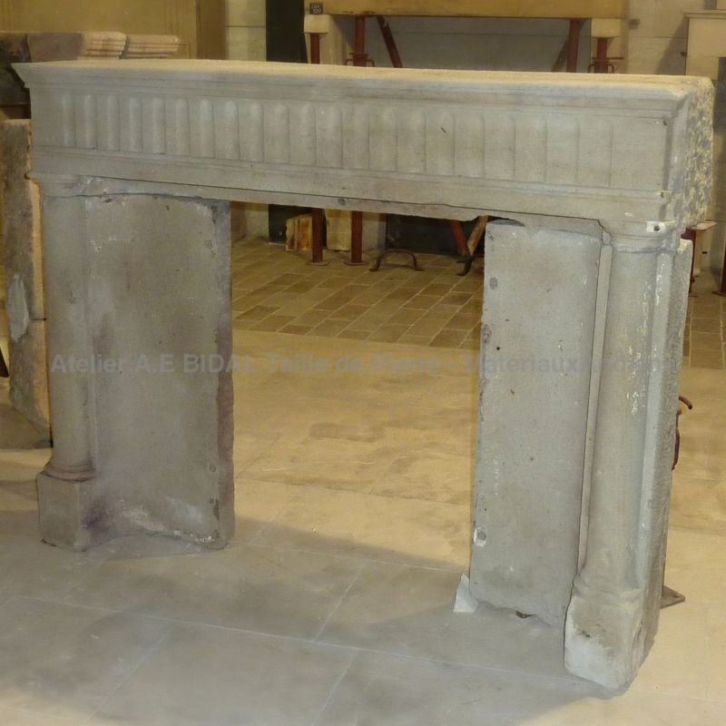 Discover the antique stone fireplace with its jambs carved in columns | Alain BIDAL workshop