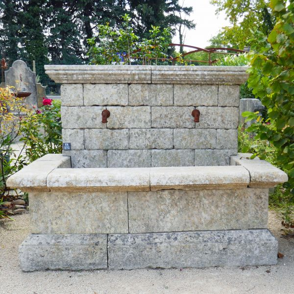 Wall fountain made of reclaimed materials : old stone and iron