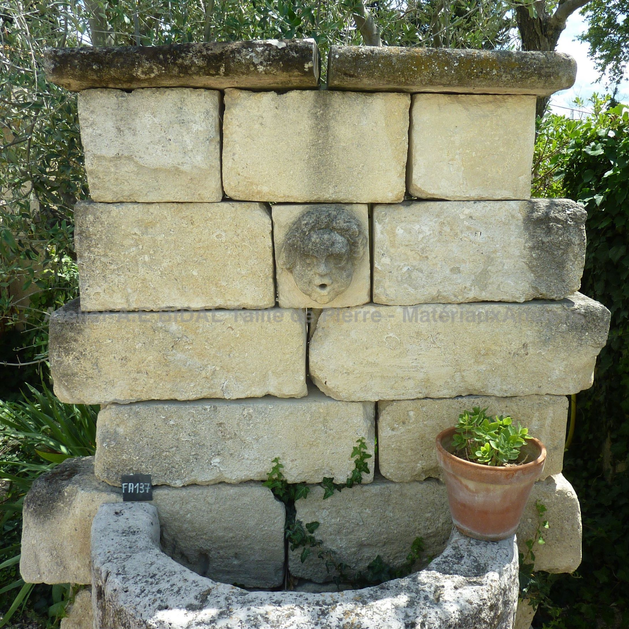 Wall fountain with semicircular basin and bonded pediment in stone.