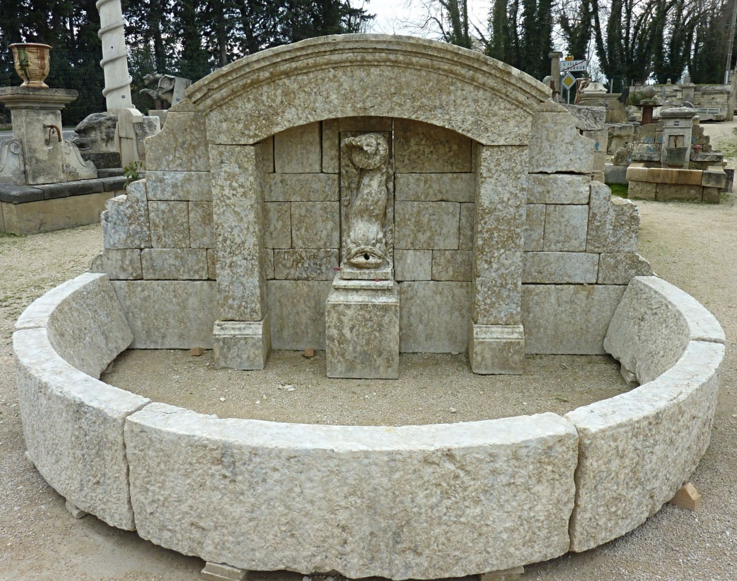 Large fountain in old stones for outdoor landscaping | Fountain with fish spitting water carved in stone.