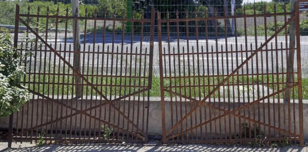 An old gate or wrought iron gate used to restrict access to a property.