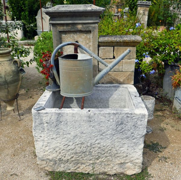 Small wall fountain in stone | Outdoor fountain with a massive stone trough.