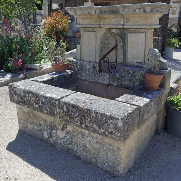 Pretty rustic wall fountain. Old fashionned stone fountain.
