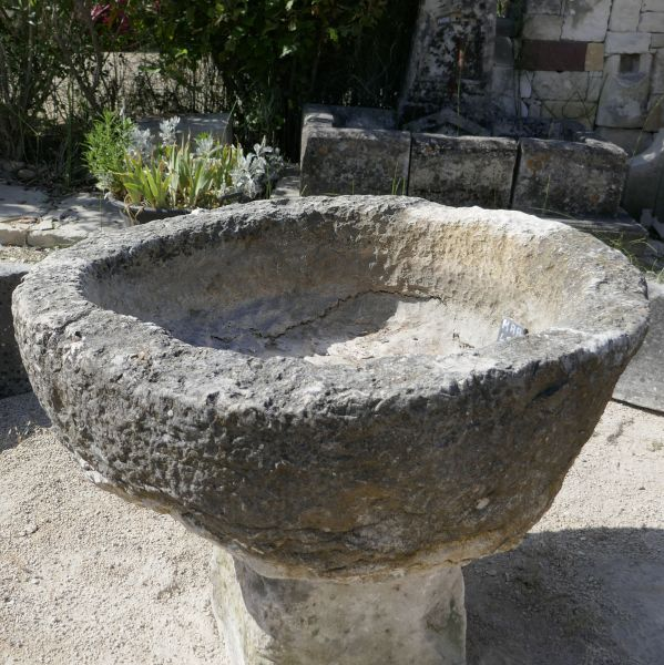 Circular basin in stone : an antique large round stone trough that can be used as a planter.