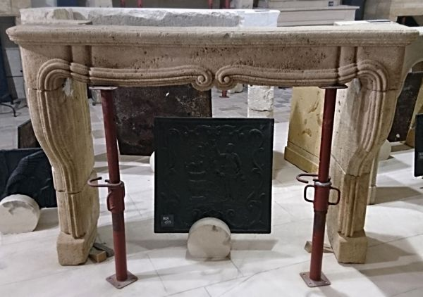 Ancient stone fireplace in a soft ocra color - beautiful decorative fireplace in a Louis 15 style.