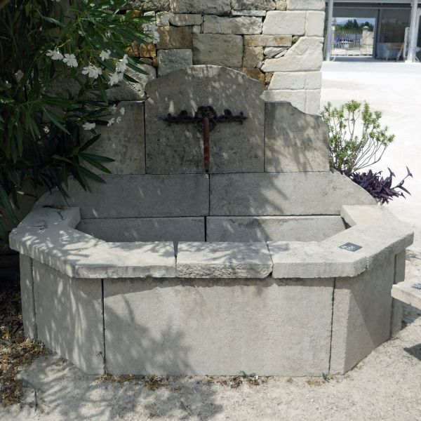 Small fountain - wall fountain made of stone and wrought iron.