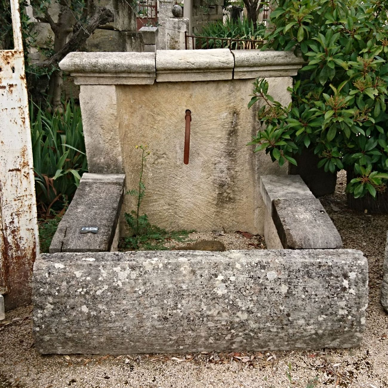 Nice rustic fountain with large copings - a stone fountain composed of a basin and a pediment.